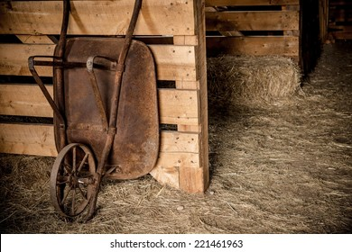 Aged Rusty Barrow in the Wooden Farm Barn. Agriculture Theme.