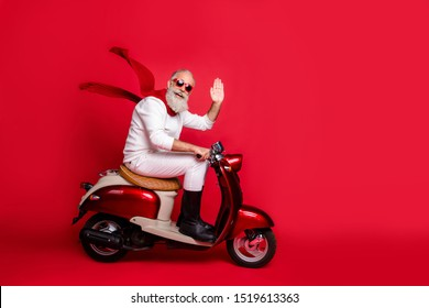 Aged santa man with grey hair move party by vintage moped wear white jumper and trousers isolated red background