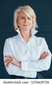 Aged self assured female portrait. Confidence and elegance. Stylish senior woman looking at camera. Arms folded.