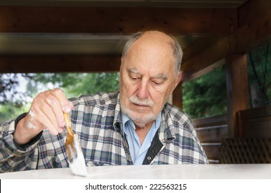 aged senior man with expressive face painting carefully  a garden  table