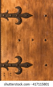 Aged shutters door board with iron decorated hinges and bolts.
