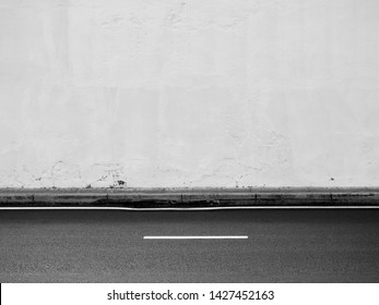 aged street white wall with asphalt road