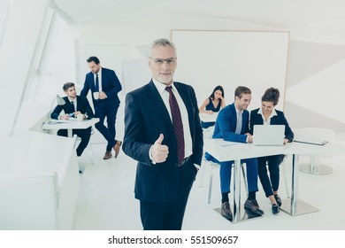 Aged successful businessman in suit showing thumb up in office