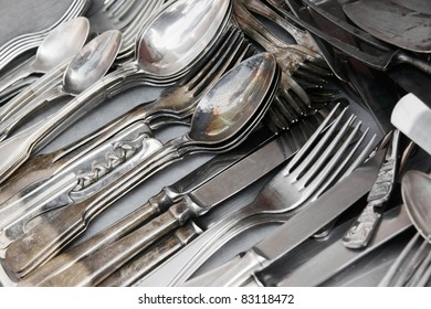 Aged and tarnished silver cutlery for sale at the flea market.