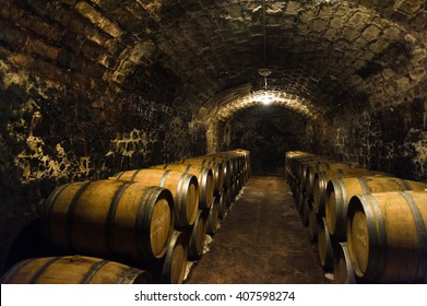 Aged traditional wooden vine barrels lined up in cool and dark vine cellar
