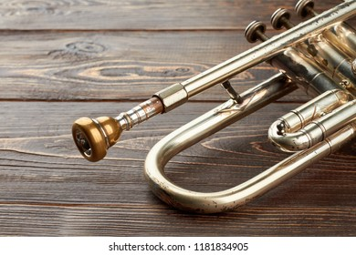 Aged trumpet on wooden background. Old trumpet with brassy mouthpiece. Classical music instrument.