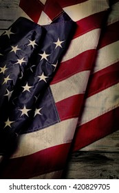 Aged US flag. Creased flag on wooden background. National banner on old table. History had its dark moments.