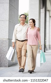 Aged Vietnamese couple walking in street with shopping bags