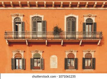 Aged vintage building facade with balcony. Vintage building facade wall. Classic European architecture. Postcard wallpaper. Vintage estate concept.