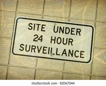 aged vintage photo of 24 hour surveillance sign