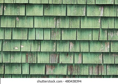 Aged and weathered green painted wood roof shingles.