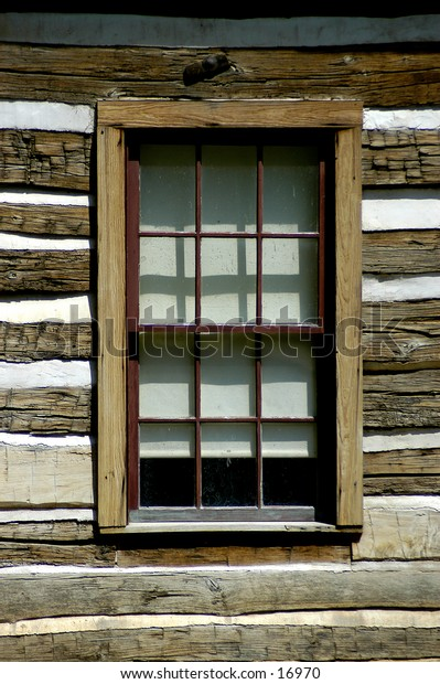 An aged window surrounded by wooden slats.