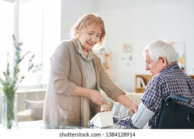 Aged woman in casualwear using tonometer to measure blood pressure of her handicapped husband at home