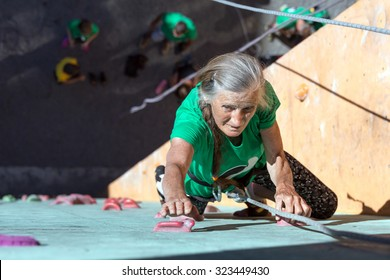 Aged Woman Climbing Wall Elderly Female Demonstrates Excellent Physical and Mental Abilities Ascending Vertical Climbing Wall Group of Climbers Staying Below on Ground
