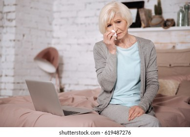 Aged woman crying while sitting on bed
