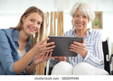 aged woman and her adult daughter using tablet
