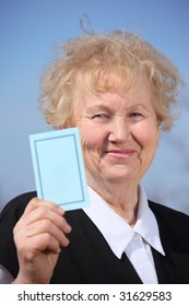 Aged woman holds card in hand on sky