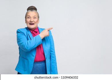 aged woman pointing finger at copy space and toothy smiling. Emotion and feelings concept. Portrait of handsome expressive grandmother with light blue suit. Studio shot, isolated on gray background