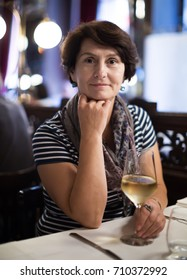 Aged woman sits at table at restaurant and holds glass with wine