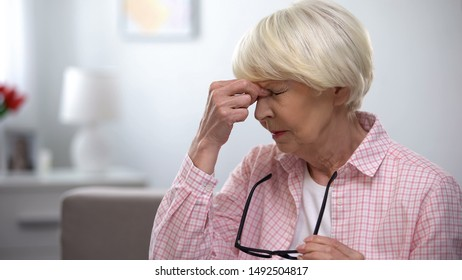 Aged woman taking off eyeglasses and massaging painful nose, migraine pain