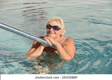Aged woman that leaned her hand to handrails of swimming pool.