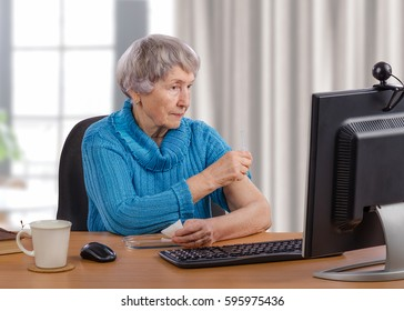 Aged woman tries to give an intramuscular injection for herself. Grey-haired lady sits at wooden desk in front of monitor and holds syringe by right hand. She receives interactive telemedicine service
