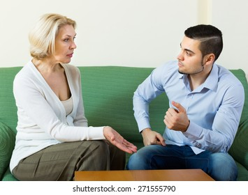 Aged woman and young guy discussing something with serious faces on sofa