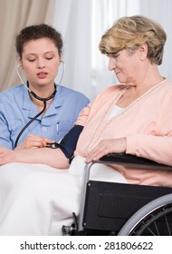 Aged woman and young nurse checking the hypertension