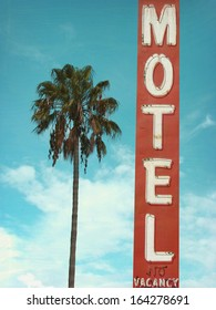 aged and worn retro photo of neon motel sign and palm tree