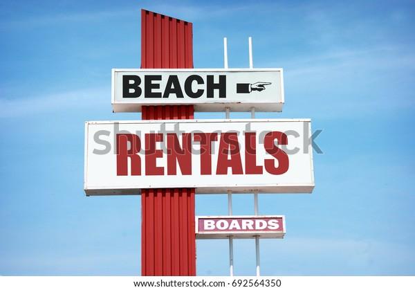 aged and worn vintage beach rentals sign