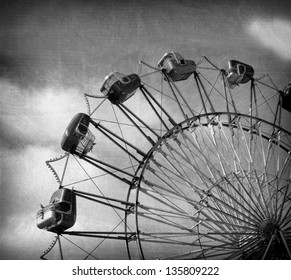 aged and worn vintage black and white photo of ferris wheel