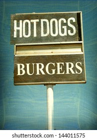 aged and worn vintage hot dogs and burgers sign