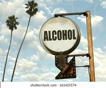 aged and worn vintage photo of alcohol sign with arrow and palm trees
