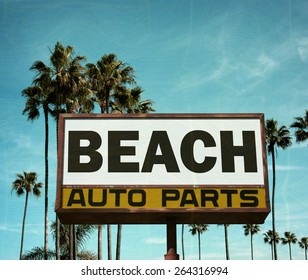 aged and worn vintage photo of auto parts sign with palm trees