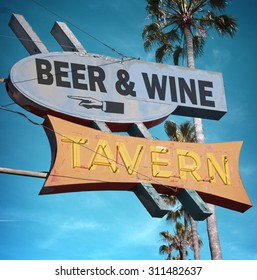 aged and worn vintage photo of beer and wine tavern neon sign
