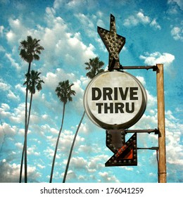 aged and worn vintage photo of drive thru sign with palm trees