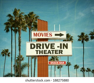 aged and worn vintage photo of drive in theater sign with pal trees
