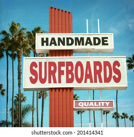 aged and worn vintage photo of handmade surfboard sign on beach