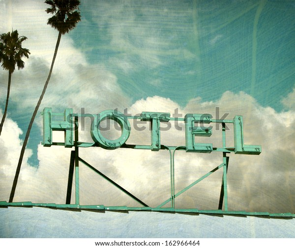 aged and worn vintage photo of hotel sign and palm trees