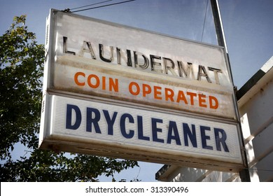 aged and worn vintage photo of laundromat and dry cleaners sign