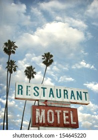 aged and worn vintage photo of motel and restaurant neon sign with palm trees