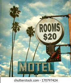 aged and worn vintage photo of motel rooms sign with palm trees