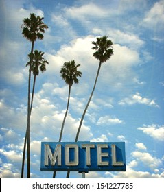 aged and worn vintage photo of neon motel sign and palm trees