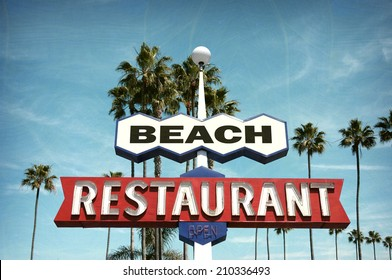 aged and worn vintage photo of neon sign on beach with palm trees