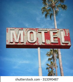 aged and worn vintage photo of neon motel sign with palm trees