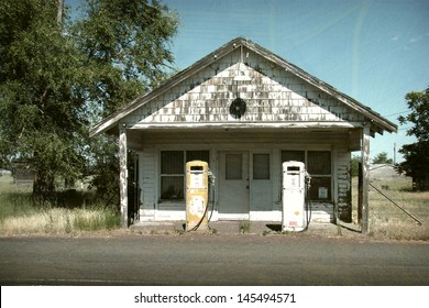 aged and worn vintage photo of old gas station and pumps
