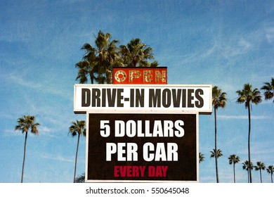 aged and worn vintage photo of old drive in movie sign with palm trees