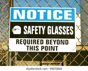 aged and worn vintage photo of safety glasses required sign