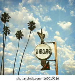 aged and worn vintage photo of surfboards sign and palm trees