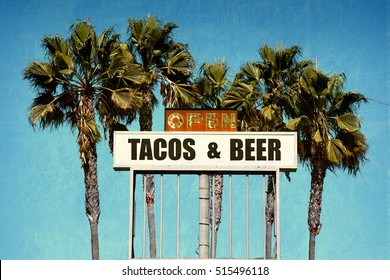 aged and worn vintage photo of tacos and beer sign with palm trees